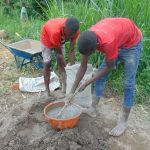 The Water Project: Emurumba Community, Makokha Spring -  Community Members Help Mix Cement