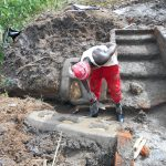 The Water Project: Kalenda A Community, Webo Simali Spring -  Cementing Stone Pitching