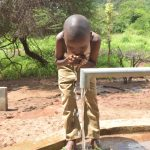 The Water Project: Wamwathi Community A -  Child Drinks From The Well