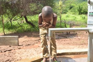 The Water Project:  Child Drinks From The Well