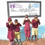 The Water Project: Nguluma Primary School -  Drinking Water From The Tank