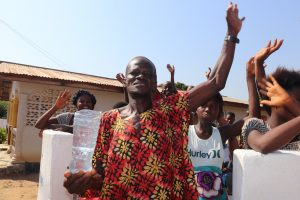 The Water Project:  Community Member Rejoicing Holding Clean Water