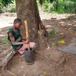 The Water Project: Rubona Kyawendera Community -  Girl Pounding Grain