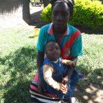 The Water Project: Mahira Community, Jairus Mwera Spring -  Alice Mwera Holding Her Baby Outside Her House