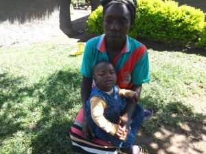 The Water Project:  Alice Mwera Holding Her Baby Outside Her House