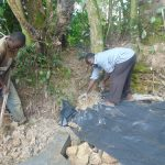 The Water Project: Bukhaywa Community, Ashikhanga Spring -  Adding The Plastic Tarp