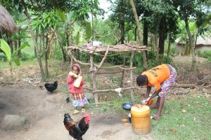 The Water Project:  Beatrice Cleans Utensils Next To Dishrack And Daughter Joy