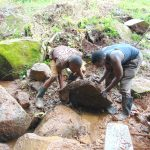 The Water Project: Chepnonochi Community, Shikati Spring -  Moving Stones Into Backfilled Area