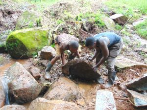 The Water Project:  Moving Stones Into Backfilled Area