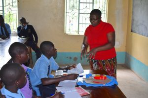 The Water Project:  Trainer Jacky Reviewing Training Materials With Pupils