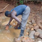The Water Project: Chepnonochi Community, Shikati Spring -  Backfilling With Stones