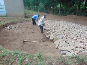 The Water Project:  Laying Stones For Rain Tank Foundation
