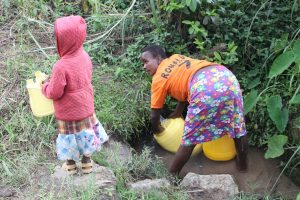 The Water Project:  Beatrice Draws Water From Unprotected Spring