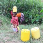 The Water Project: Litinye Community, Shivina Spring -  Baby Joy Carrying Her Own Water From The Spring