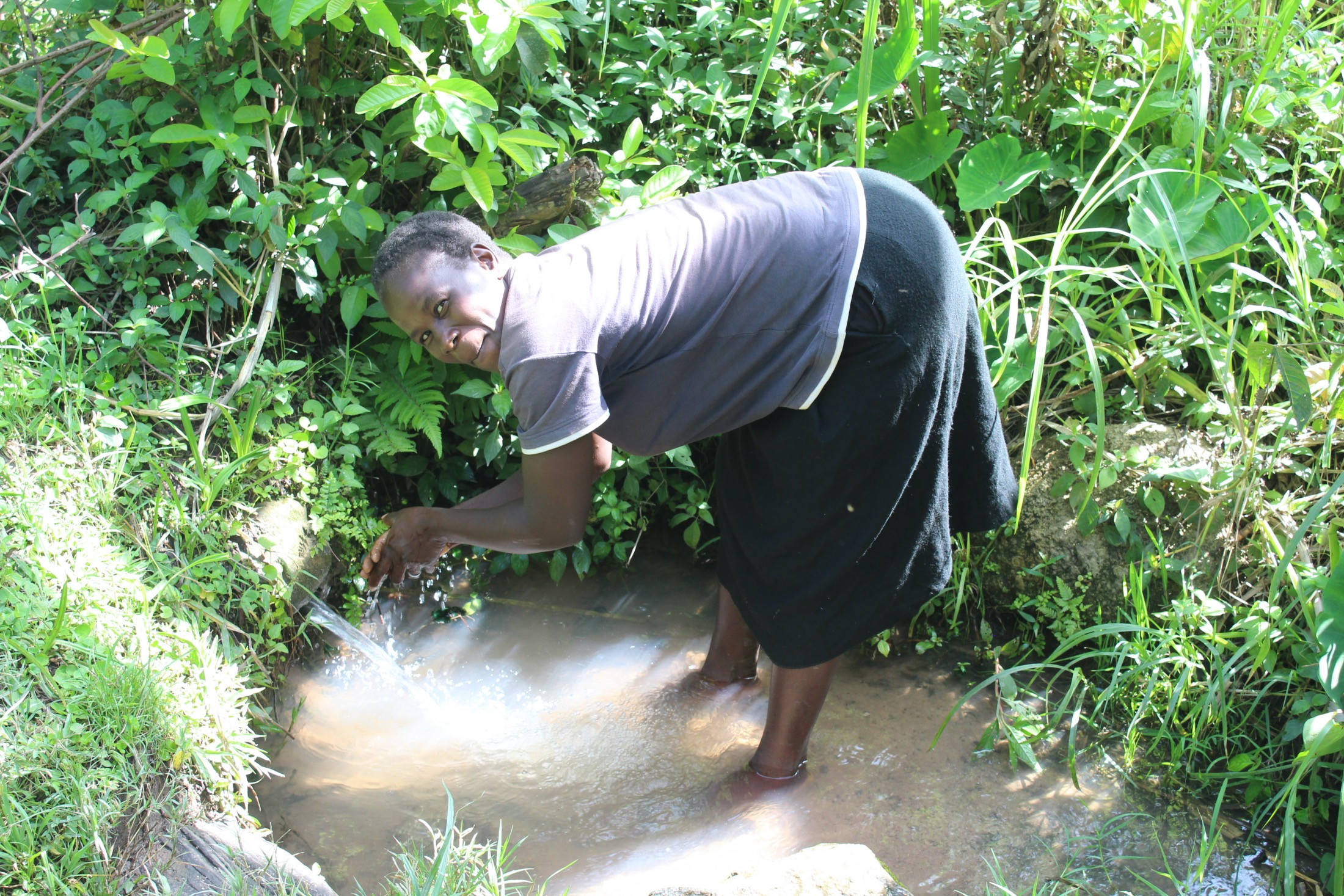 The Water Project : 24-kenya20172-a-woman-waashing-hands-at-the-spring