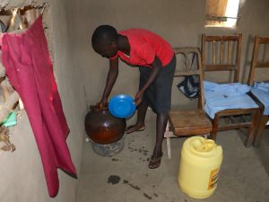 The Water Project:  Drawing Water From Storage Pot