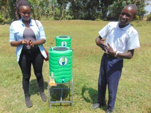 The Water Project:  Pupil And Facilitator Demonstrate Handwashing