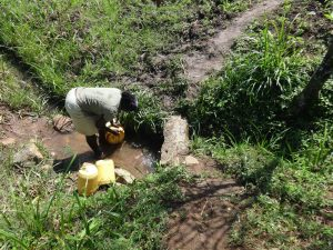 The Water Project:  Washing Her Container Before Fetching Water