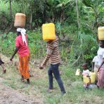The Water Project: Litinye Community, Shivina Spring -  Community Members Carrying Water From Unprotected Spring