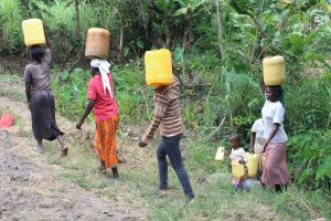 The Water Project:  Community Members Carrying Water From Unprotected Spring