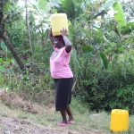 The Water Project: Litinye Community, Shivina Spring -  Community Member Carrying Water