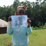 The Water Project: Chepnonochi Community, Shikati Spring -  Community Health Volunteer Nancy Khagai Shows A Training Poster