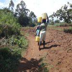The Water Project: Mahira Community, Jairus Mwera Spring -  Carrying Water From Spring