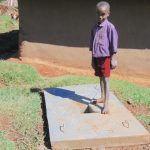 The Water Project: Chepnonochi Community, Shikati Spring -  A Boy With His Familys New Sanitation Slab