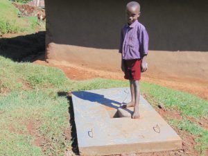 The Water Project:  A Boy With His Familys New Sanitation Slab