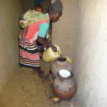 The Water Project: Mahira Community, Jairus Mwera Spring -  Pouring Water Into Storage Pot