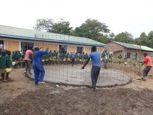 The Water Project:  Students Watch Wire Placement Over Foundation