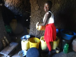 The Water Project:  A Child Pours Water Into Kitchen Storage Containers