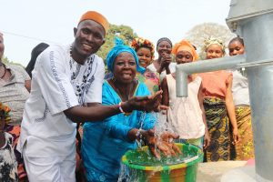 The Water Project:  Town Chief And Old Woman Splashing Clean Water