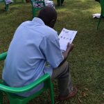 The Water Project: Shirakala Community, Ambani Spring -  A Community Member Reading Through The Manual