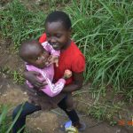 The Water Project: Emukoyani Community, Ombalasi Spring -  A Boy Carries His Sister To Training
