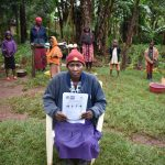 The Water Project: Namarambi Community, Iddi Spring -  A Community Member Holding Their Informational Pamphlet