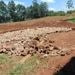 The Water Project: Jinjini Friends Primary School -  Laying Stones On Excavated Ground