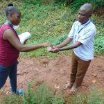 The Water Project: Shitaho Community, Mwikholo Spring -  Sanitizing Participants Hands Before Training Begins