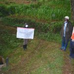 The Water Project: Maganyi Community, Bebei Spring -  Sir Erick With The Chart At The Spring With Community Members