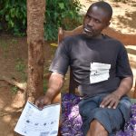 The Water Project: Musango Community, M'muse Spring -  A Community Member With Issued Pamphlets