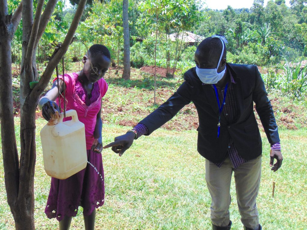 The Water Project : 10-kenya4712-covid19-handwashing-with-leaky-tin-demonstration-1