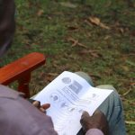 The Water Project: Emachembe Community, Hosea Spring -  A Community Member Reads Informational Pamphlet