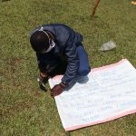 The Water Project: Asimuli Community, John Omusembi Spring -  Trainer Samuel Nailing The Chart Onto The Poles