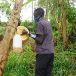 The Water Project: Busichula Community, Marko Spring -  Trainer Protus Fills The Leaky Tin At The Spring