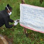 The Water Project: Namarambi Community, Iddi Spring -  Installing Covid Reminder Chart At The Spring