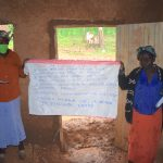 The Water Project: Maganyi Community, Bebei Spring -  Holding Up The Prevention Reminder Chart