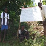 The Water Project: Chegulo Community, Yeni Spring -  Posing Next To The Chart