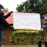 The Water Project: Malava Community, Ndevera Spring -  Trainers Go Through Prevention Reminders Chart