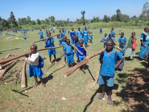 The Water Project:  Pupils Carry Poles To Insert For Dome Support
