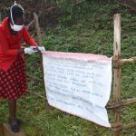 The Water Project: Ibinzo Community, Lucia Spring -  Installing Caution Chart At The Spring